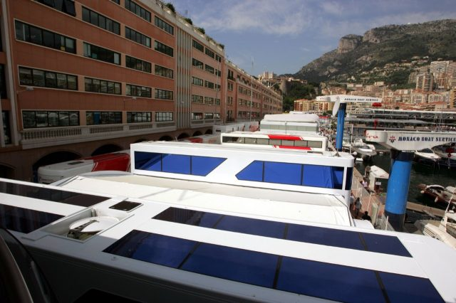 The teams' motorhomes are squeezed between buildings and the harbour in the paddock
