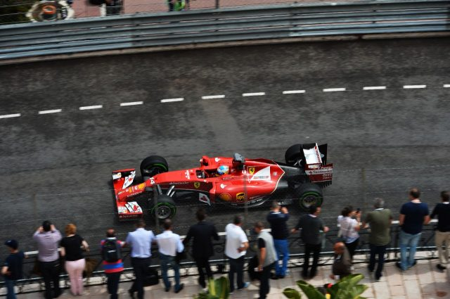 Specatators watch Fernando Alonso (ESP) Ferrari F14 T.