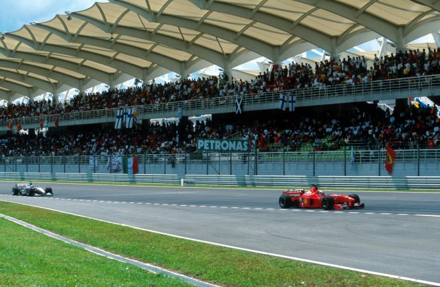 Michael Schumacher(GER) Ferrari F399 leads Hakkinen in front of the impressive Grandstand