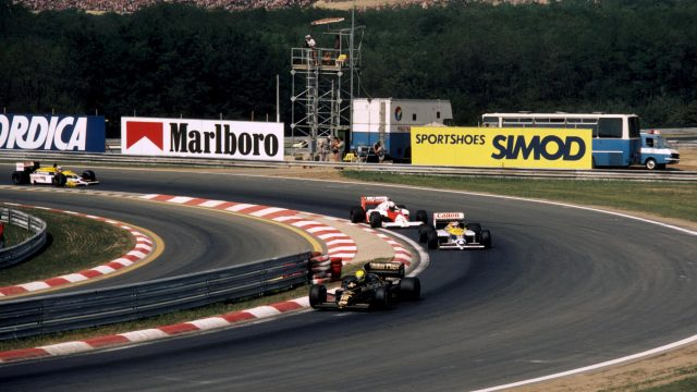 Second place finisher Ayrton Senna (BRA) Lotus 98T leads the eventual winner Nelson Piquet (BRA) Williams FW11 and Alain Prost (FRA) McLaren MP4/2C who had an accident and retired. Hungarian Grand Prix, Hungaroring, 10 August 1986.