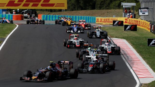 Carlos Sainz (ESP) Scuderia Toro Rosso STR11 and Jenson Button (GBR) McLaren MP4-31 at the start of the race at Formula One World Championship, Rd11, Hungarian Grand Prix, Race, Hungaroring, Hungary, Sunday 24 July 2016. &copy&#x3b; Sutton Images