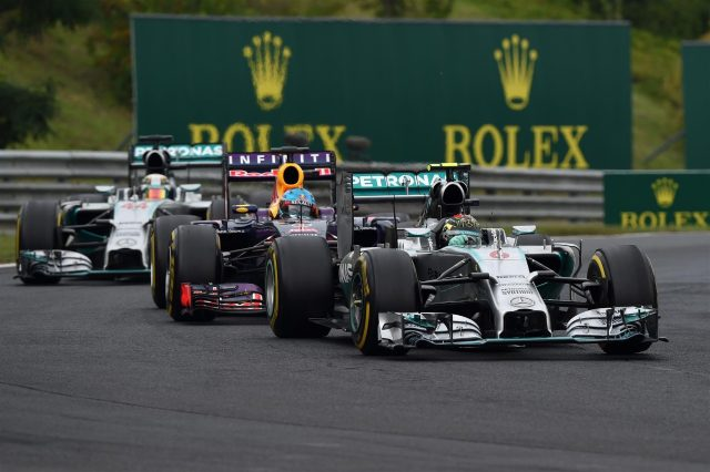 Nico Rosberg (GER) Mercedes AMG F1 W05 leads Sebastian Vettel (GER) Red Bull Racing RB10 and Lewis Hamilton (GBR) Mercedes AMG F1 W05. Formula One World Championship, Rd11, Hungarian Grand Prix, Race Day, Hungaroring, Hungary. Sunday, 27 July 2014. © Sutton Images