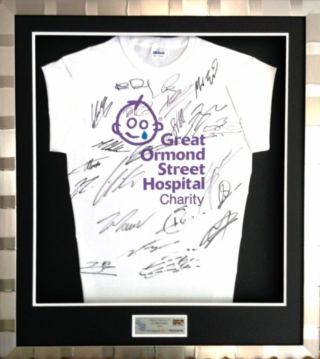 The StarCards framed t-shirt signed by the Formula 1 drivers. The drivers and teams of the Formula One world have again supported the annual StarCards F1 charity auction, supporting Great Ormond Street Childrens Hospital in London. They will be auctioned at www.starcards.org during the period of the 2014 British Grand Prix. Starting at 8pm on the 30th June and finishing at 8pm on the 10th July. 2014 Formula One Starcards charity auction, London, England, 1 July 2014.