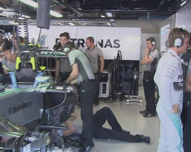 Nico Rosberg watches the action from the Mercedes garage, while his mechanics work on a gearbox issue that rules him out of FP3. © FOWC Ltd