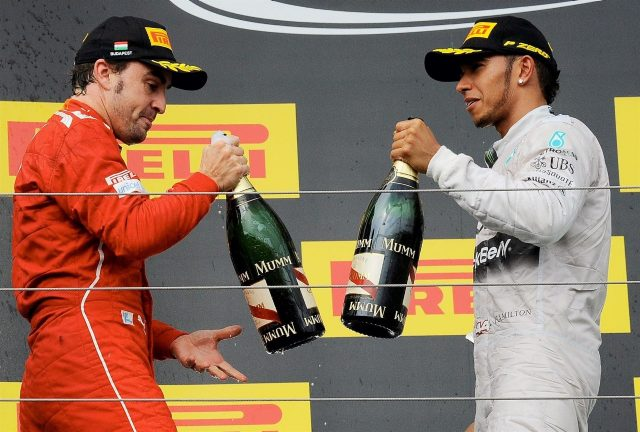 Fernando Alonso (ESP) Ferrari and Lewis Hamilton (GBR) Mercedes AMG F1 celebrate on the podium with the champagne. Formula One World Championship, Rd11, Hungarian Grand Prix, Race Day, Hungaroring, Hungary. Sunday, 27 July 2014